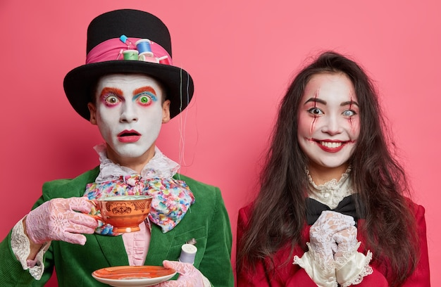 Plan horizontal d'un chapelier mâle choqué pose avec tasse sur le thé. heureuse femme brune a des blessures sanglantes de maquillage effrayant sur le visage