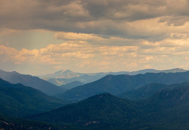 Plan horizontal de collines dans différentes nuances de bleu et le ciel nuageux du soir