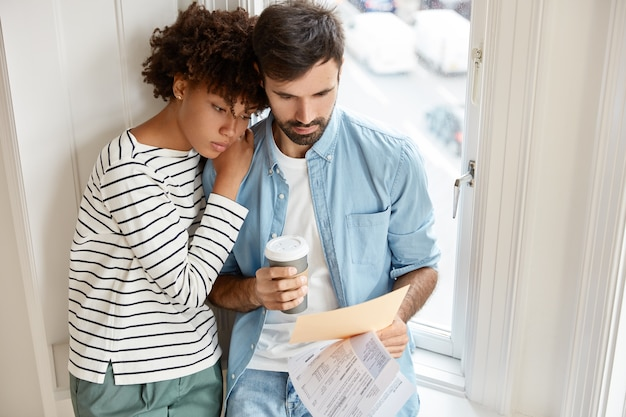 Plan horizontal du charmant petit ami et petite amie se tiennent près de la fenêtre
