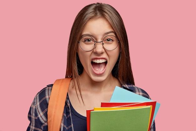 Plan horizontal d'un élève maussade mécontent s'exclame avec des émotions négatives, garde la bouche largement ouverte