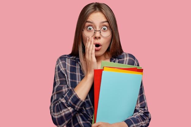 Plan horizontal d'une étudiante étonnée retient son souffle, regarde avec les yeux sortis