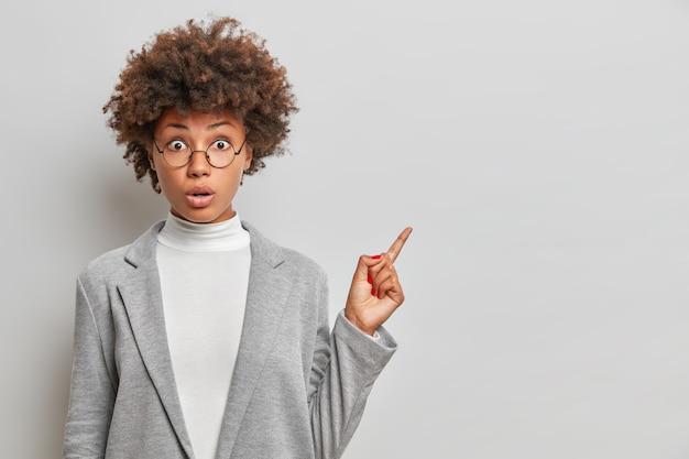 Plan horizontal d'une femme d'affaires ethnique choquée a les cheveux bouclés touffus