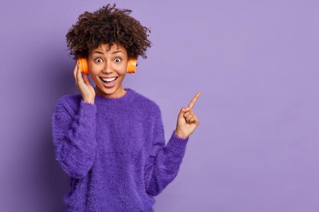Plan horizontal d'une femme afro-américaine assez joyeuse écoute de la musique agréable dans les points d'écouteurs à droite porte des poses de cavalier occasionnel