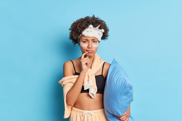 Plan horizontal d'une femme afro-américaine mécontente aux cheveux bouclés applique des patchs de collagène sous les yeux subit des traitements de beauté