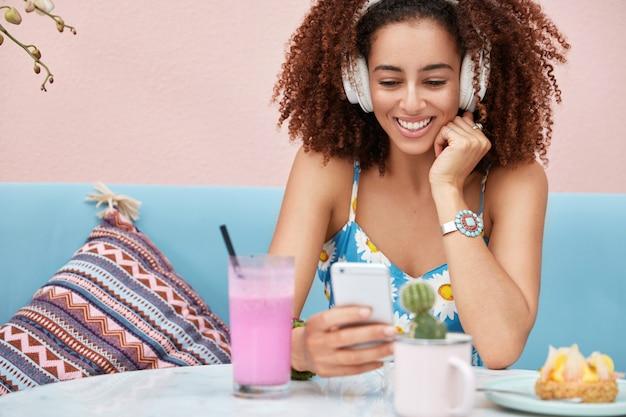 Plan horizontal d'une femme afro-américaine à la peau sombre heureuse écoute de la musique à partir d'un site web de radio, connecté à internet sans fil