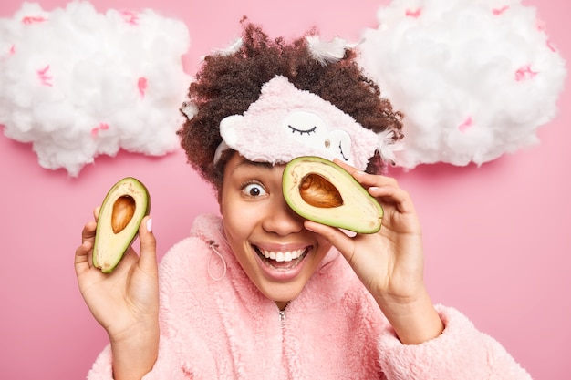 Plan horizontal d'une femme afro-américaine positive utilise un produit cosmétique naturel couvre le visage avec des moitiés d'avocat sourit largement vêtu d'un costume de pyjama isolé sur un mur rose