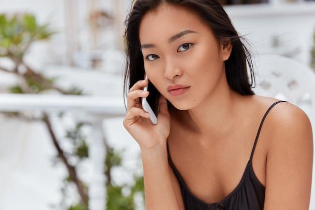Plan horizontal d'une femme à l'air agréable avec une apparence attrayante, parle via un téléphone intelligent avec une expression sérieuse, s'assoit à une cafétéria extérieure, attend un partenaire commercial. les gens, la technologie, le repos