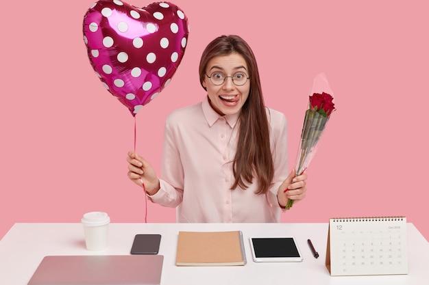 Plan horizontal d'une femme assez positive, lèche les lèvres avec la langue, porte des lunettes rondes et une chemise, se sent heureux