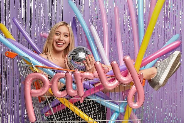 Plan horizontal d'une femme blonde heureuse a du maquillage, détient une boule disco