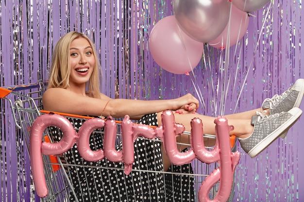 Plan horizontal d'une femme blonde optimiste s'amuse à la fête d'anniversaire