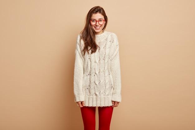 Plan horizontal d'une femme européenne positive en vêtements d'hiver blancs et collants rouges, pose sur un mur beige, bénéficie de temps libre, d'être de bonne humeur. personnes, émotions, expressions faciales