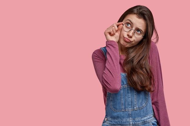 Plan horizontal d'une femme européenne rêveuse fait peu de signe avec la main, porte des lunettes et une salopette en denim