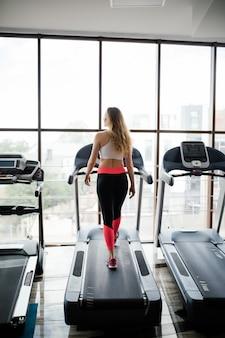 Plan horizontal d'une femme faisant du jogging sur un tapis roulant au club de santé. femme travaillant dans une salle de sport fonctionnant sur un tapis roulant.