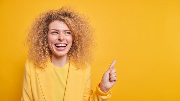 Plan horizontal d'une femme heureuse aux cheveux bouclés qui sourit à pleines dents donne une recommandation