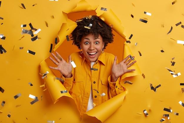 Plan horizontal d'une femme joyeuse avec une coiffure afro, heureuse de voir une personne proche, lève les paumes, porte une tenue élégante excitée à poser dans un trou de papier avec des étincelles volantes