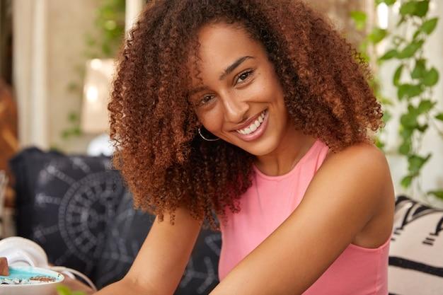 Plan horizontal d'une femme joyeuse à la peau sombre a les cheveux croquants, porte un gilet rose décontracté, sourit largement, pose à la terrasse sur le canapé, exprime des émotions positives, a du temps libre