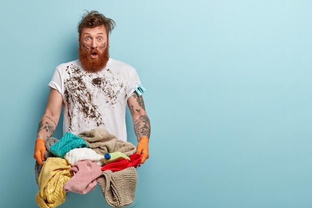 Plan horizontal d'une femme de ménage stupéfaite porte un panier à linge, a des vêtements sales