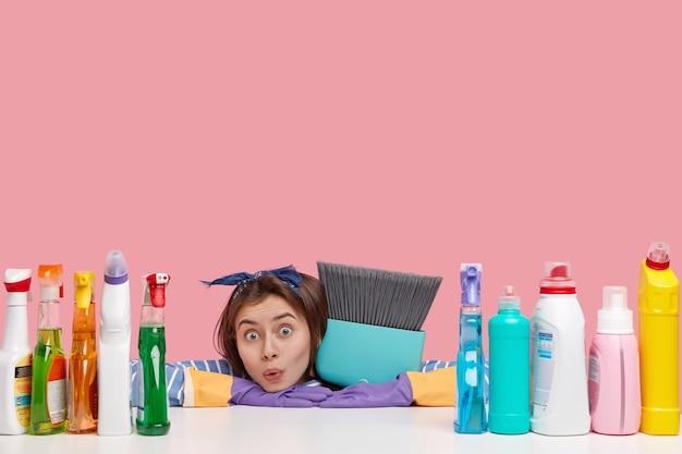 Plan horizontal d'une femme de ménage surprise regarde dans la stupeur, s'appuie sur les mains sur la table, porte un balai, entouré de nombreux produits de nettoyage polyvalents