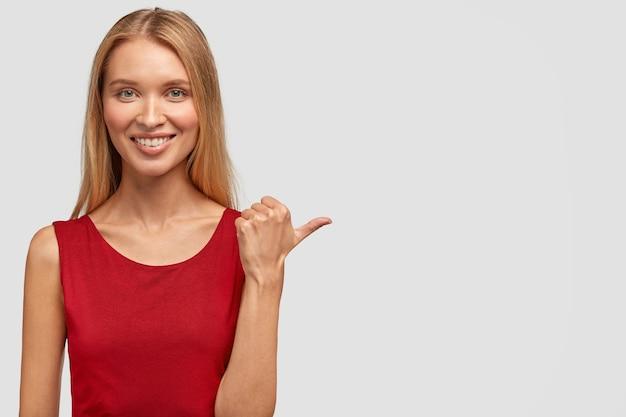 Plan horizontal d'une femme mince assez heureuse a un sourire doux, un regard attrayant, des points avec le pouce de côté, vêtu d'un t-shirt rouge