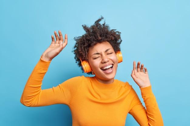 Plan horizontal d'une femme optimiste aux cheveux bouclés dansant au rythme de la musique apprécie sa liste de lecture préférée porte des écouteurs stéréo sur les oreilles attrape chaque morceau chante une chanson isolée sur un mur bleu