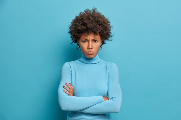 Plan horizontal d'une femme à la peau sombre garde les bras croisés et regarde avec une expression offensée