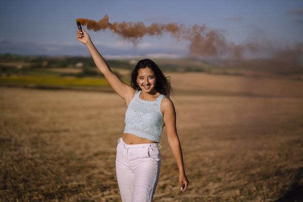 Plan horizontal d'une femme posant avec une bombe fumigène sur un fond de champs et de moulins à vent