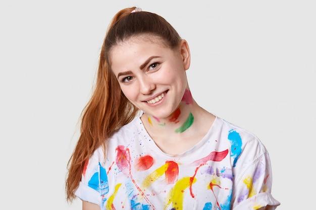 Plan horizontal d'une femme avec une queue de cheval, incline la tête, a une occupation créative, vêtu d'un t-shirt décontracté avec des taches d'aquarelle, pose sur blanc. personnes et inspiration