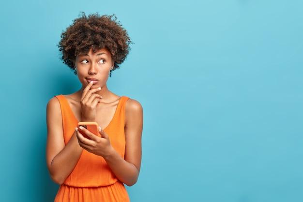 Plan horizontal d'une femme réfléchie tient en main un smartphone moderne attend l'appel réfléchit au contenu du message porte des modèles de robe oramge contre l'espace de copie de mur bleu de côté