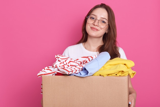 Plan horizontal de femme souriante posant isolé sur rose et tenant une boîte avec des vêtements plausibles, des vêtements pour la maison des enfants ou des pauvres, charmante jeune femme faisant une charité.