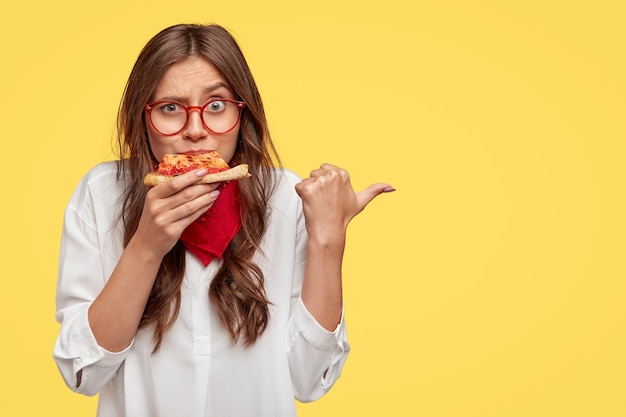 Plan horizontal d'une femme surprise mange une tranche de pizza savoureuse, vêtue de vêtements à la mode, indique avec le pouce, vous invite à la pizzeria, isolée sur un mur jaune. les gens et la nutrition