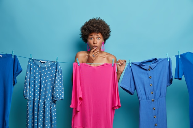 Plan horizontal d'une femme surprise à la peau sombre qui fait face à un problème de quoi porter, se tient devant une robe rose, a une expression stupéfaite, pose près d'une corde avec des robes lavées suspendues. il est temps de s'habiller.
