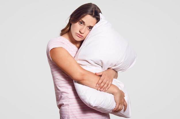 Plan horizontal d'une femme triste sérieuse porte un oreiller blanc de près, porte un pyjama, regarde directement la caméra, pose sur le blanc, veut se reposer, prêt à dormir, fait de beaux rêves