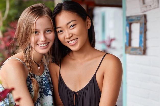 Plan horizontal de femmes heureuses s'assoient près les unes des autres, ont une véritable amitié