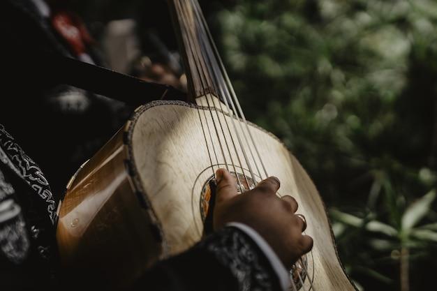 Plan horizontal d'une guitare beige acoustique jouée par un homme