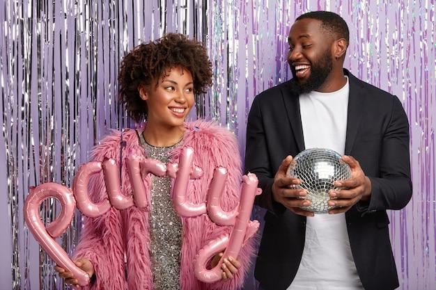 Plan horizontal d'heureux homme et femme à la peau sombre s'amusent ensemble, viennent en club, organisent une soirée disco