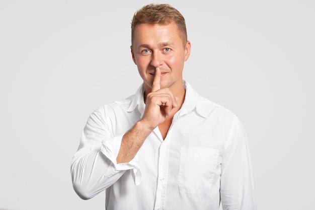 Plan horizontal d'un homme aux yeux bleus confiant fait un geste de chut