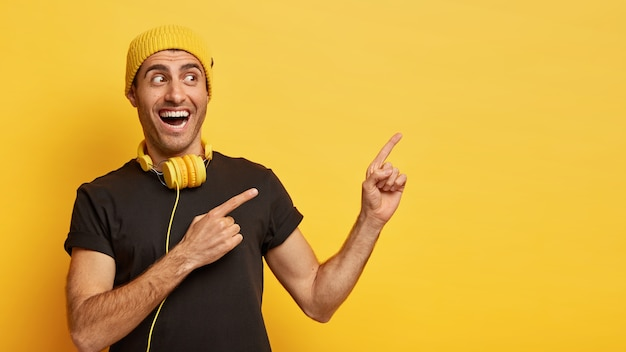 Plan horizontal d'un homme européen heureux pointe de côté avec deux index, vêtu de vêtements noirs et jaunes élégants, porte des écouteurs modernes autour du cou pour écouter la chanson
