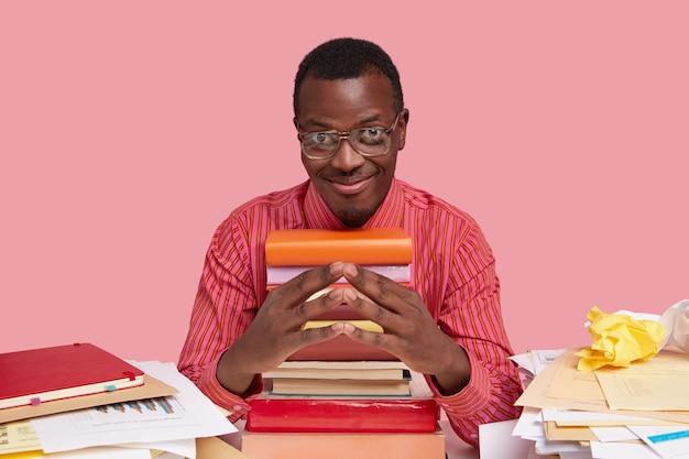 Plan horizontal d'un homme à la peau sombre a l'intention, garde les mains jointes, se sent heureux, porte des lunettes