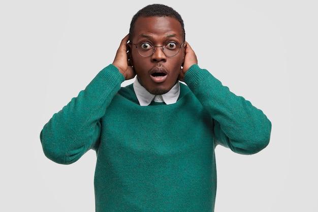 Plan horizontal d'un homme à la peau sombre stupéfié garde la main sur la tête, regarde avec stupeur, a une courte coupe de cheveux afro
