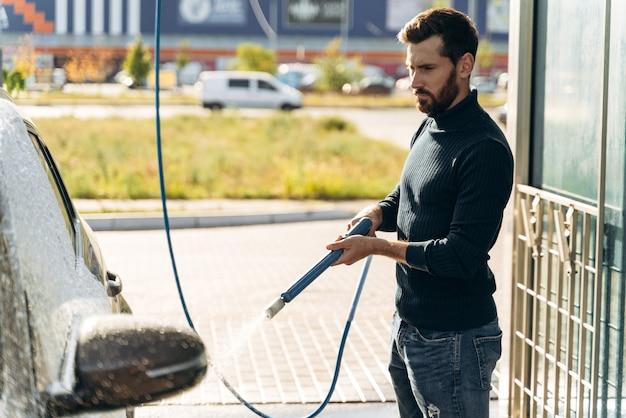 Plan horizontal d'un homme de race blanche utilisant un pulvérisateur à haute pression avec de la mousse de nettoyage sur sa voiture noire au service de lavage de voiture à l'extérieur. concept extérieur de voiture propre