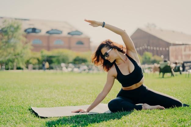 Plan horizontal d'une jeune femme modèle motivée a une séance d'entraînement matinale régulière lève le bras et se penche de différents côtés vêtus de poses de vêtements de sport sur le karemat à l'extérieur reste en bonne forme physique