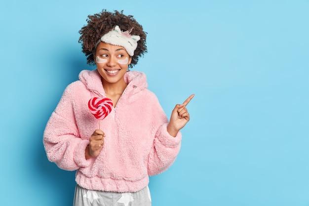 Plan horizontal de jeune femme sourit agréablement pointe à l'espace de copie détient sucette vêtue de vêtements de nuit applique des patchs de collagène isolés sur mur bleu
