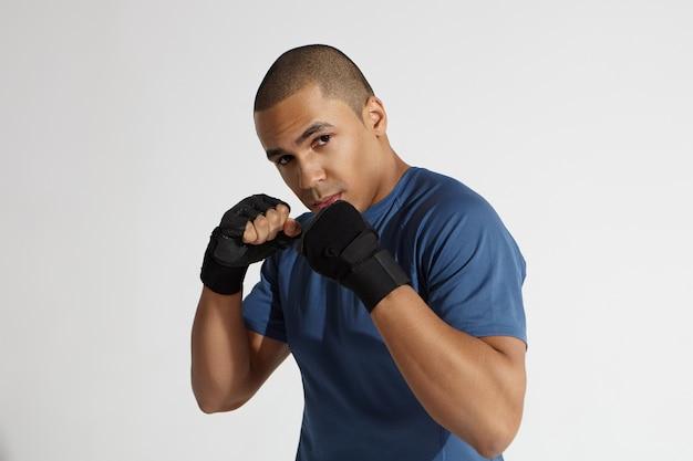 Plan horizontal d'un jeune homme afro-américain déterminé avec un corps atheltique portant des gants d'entraînement posant en position défensive, tenant des poings pompés devant son visage et regardant la caméra