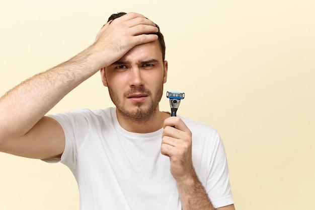 Plan horizontal d'un jeune homme caucasien effrayé émotionnel tenant un rasoir de sécurité et gardant la main sur la joue ayant peur de se raser.