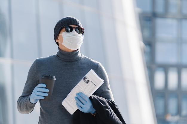 Plan horizontal d'un jeune homme dans un masque médical empêche la pneumonie infectieuse, la pandémie de coronavirus, l'épidémie de virus, boit du café pour aller, aller travailler, pose à l'extérieur, a une expression réfléchie