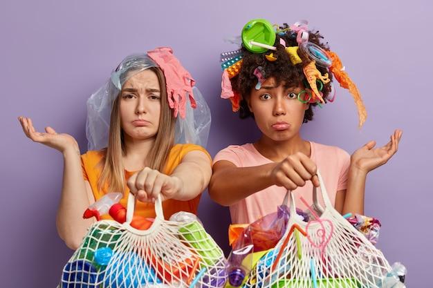 Plan horizontal de jeunes femmes déprimées posant avec des ordures sur eux