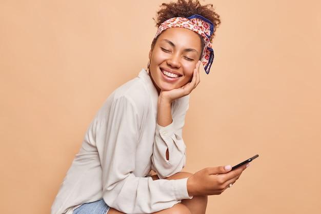Plan horizontal d'une jolie femme ethnique millénaire sourit joyeusement garde les yeux fermés parcourt le téléphone portable porte une chemise et un foulard noués sur la tête isolés sur un mur beige