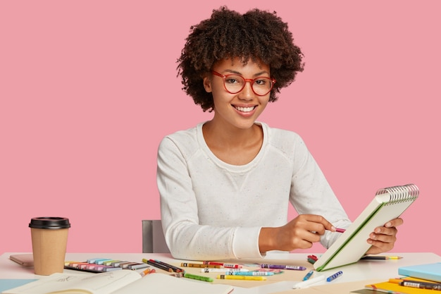 Plan horizontal de joyeux peintre afro-africain porte des lunettes à jante rouge, fait des croquis dans un cahier à spirale avec un crayon, apprécie une boisson aromatique, entouré de papeterie, sourit positivement