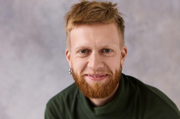 Plan horizontal d'un mec aux cheveux roux à la mode attrayant avec chaume et percé exprimant de vraies émotions positives, avec un large sourire. insouciant mignon jeune homme mal rasé souriant