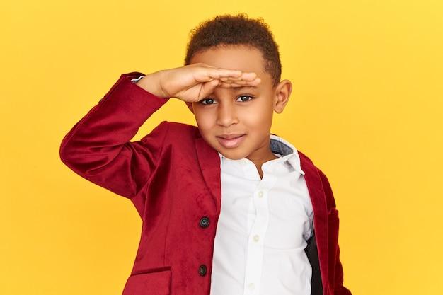 Plan horizontal d'un petit garçon à la peau sombre et curieux aux yeux perçants, regardant l'horizon, tenant la main sur son front, regardant au loin, cherchant quelque chose